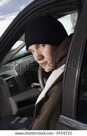Caucasian male teenager sitting in car looking back at viewer. - stock photo