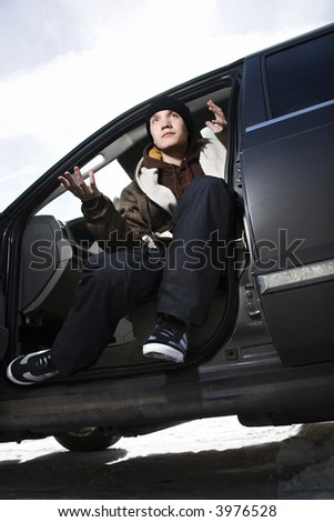 Caucasian male teenager sitting in car making hand gesture. - stock photo