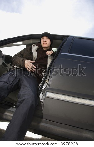 Caucasian male teenager sitting in SUV. - stock photo