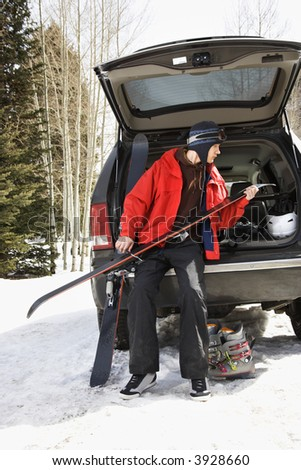 Caucasian male teenager sitting on back of SUV holding skis. - stock photo