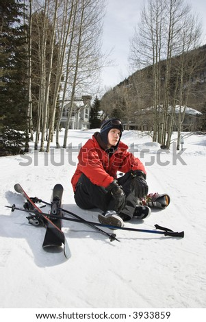 Caucasian male teenager sitting on snow with ski gear. - stock photo