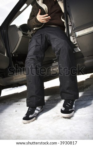 Caucasian male teenager stepping out of SUV. - stock photo