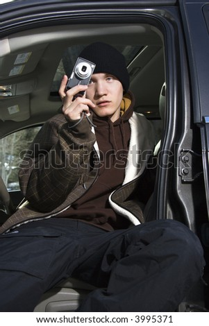Caucasian male teenager taking a picture from his car. - stock photo