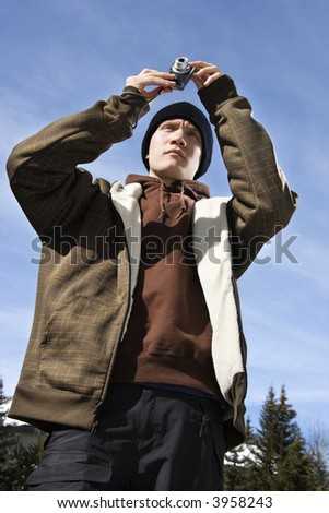 Caucasian male teenager taking a picture with a digital camera. - stock photo