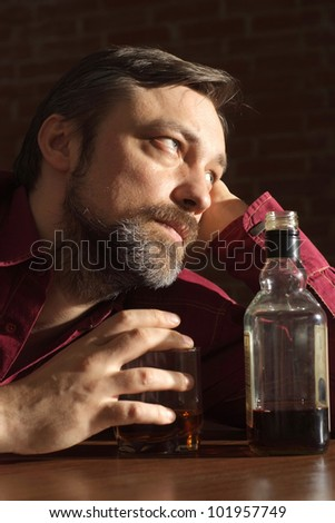 Caucasian male with a nice bottle sitting on a dark background - stock photo