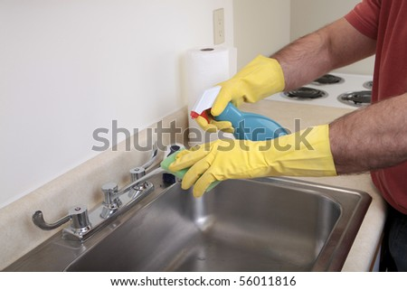 Caucasian male with dish gloves cleans the sink - stock photo