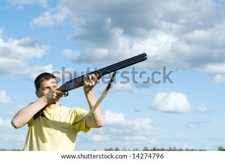 Caucasian man aiming. Cloudy sky background. - stock photo