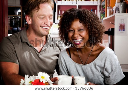 Caucasian man and African American woman in coffee house - stock photo