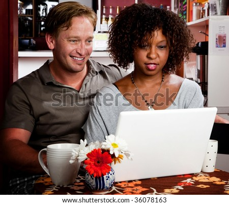 Caucasian man and African American woman in coffee house with laptop computer - stock photo