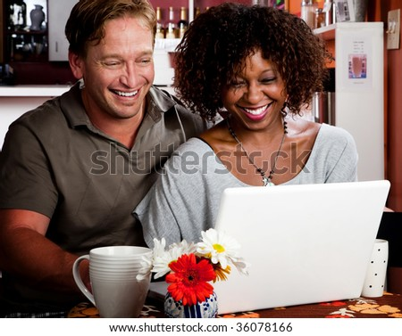 Caucasian man and African American woman in coffee house with laptop computer