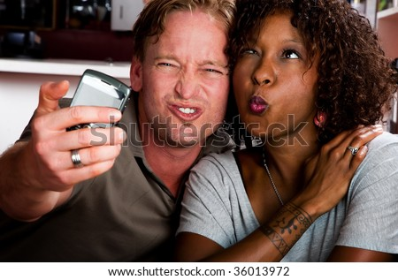 Caucasian man and African American woman taking picture in coffee house with cell phone - stock photo