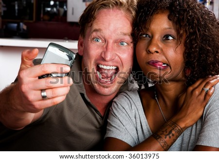 Caucasian man and African American woman taking picture in coffee house with cell phone
