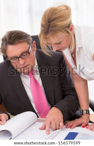 Caucasian man and woman reading a document in office - businesspeople team. - stock photo