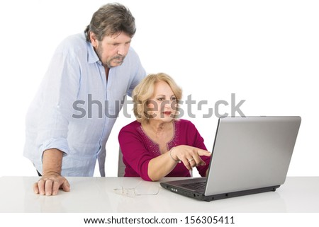 Caucasian man and woman watching a laptop.
