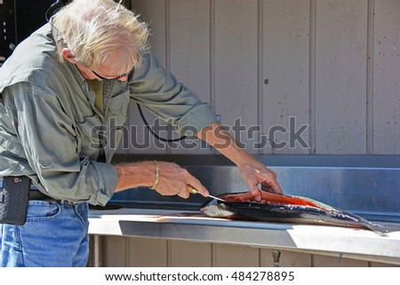 Caucasian man cleaning a salmon at fish cleaning station