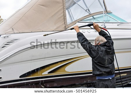 Caucasian man cleaning power boat hull with power washer