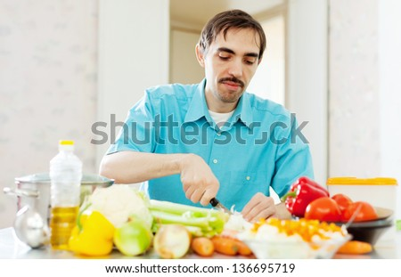 Caucasian man cooking dinner with vegetables at home kitchen - stock photo