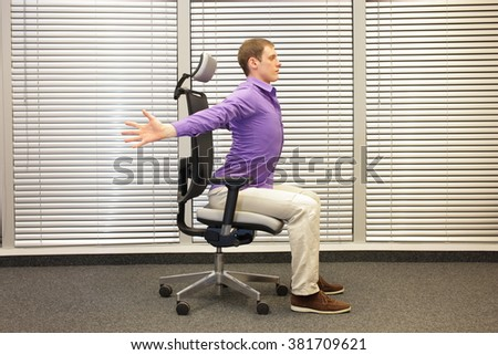 caucasian man exercising on chair in office, healthy lifestyle - stock photo