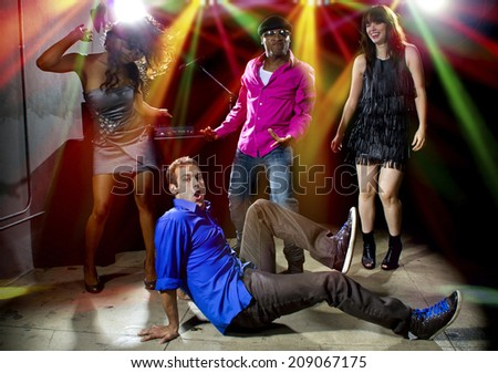 Caucasian man falls but confidently plays cool in a dance club - stock photo