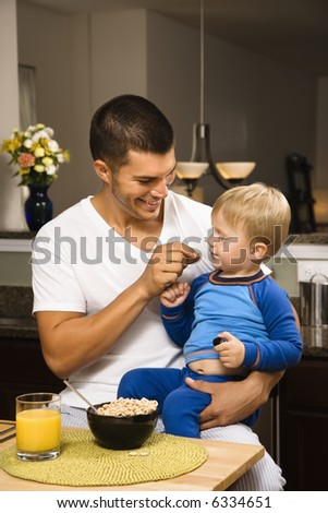 Caucasian man feeding toddler son on lap in kitchen. - stock photo