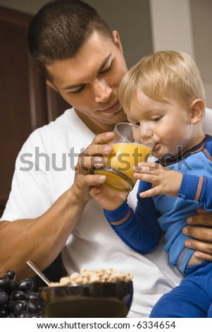 Caucasian man helping toddler son drink juice. - stock photo