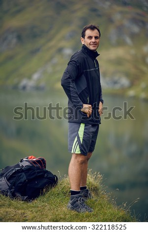 Caucasian man hiker resting near the mountain lake - stock photo