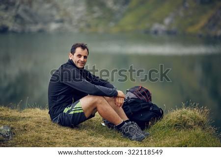 Caucasian man hiker resting near the mountain lake - stock photo