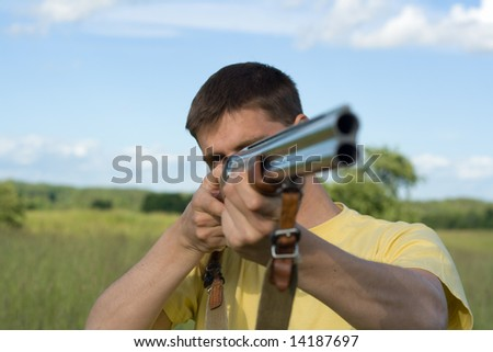 Caucasian man holding a rifle. Blue sky and grass in a background, focus on hand.