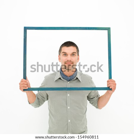 caucasian man holding an empty frame in front of him, on white background - stock photo