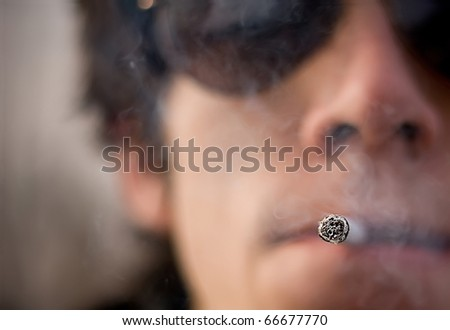 Caucasian man holding 1 cigar in his mouth. defocused background - stock photo