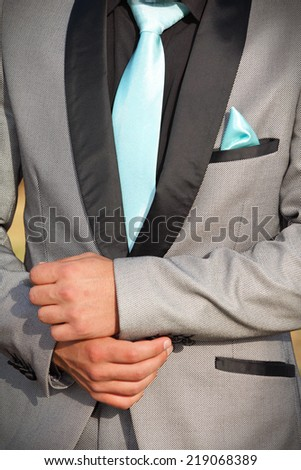 Caucasian man in a silver-grey formal suit with black trimmings. His hands are shown in front of his waist. He is wearing a turquoise tie and pocket handkerchief. - stock photo