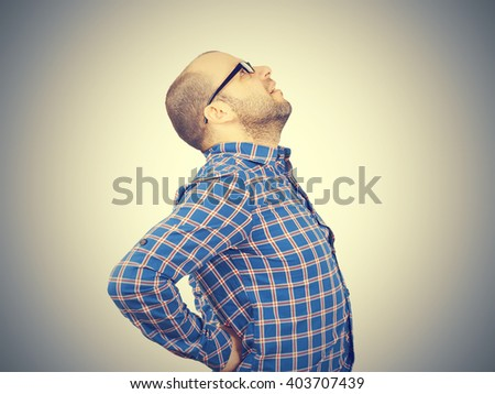Caucasian man in blue shirt struggles with intense back pain on gray background.      - stock photo