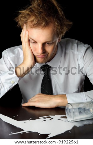 Caucasian man in business attire is upset about his spilled milk, isolated on black - stock photo