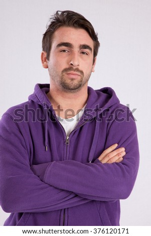 Caucasian man in purple sweatshirt with a hood looking thoughtful with his arms crossed - stock photo