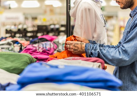 Caucasian man is buying clothes in a shop - concept about shopping - stock photo