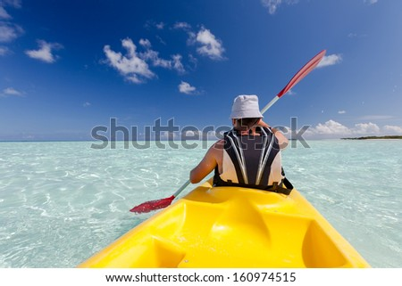 Caucasian man kayaking in sea at Maldives  - stock photo