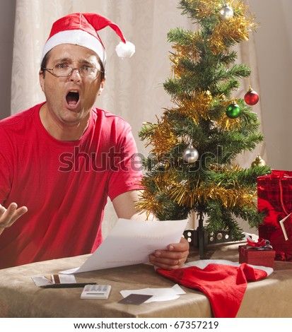 Caucasian man looking at the disastrous Xmas budget and expenses. - stock photo