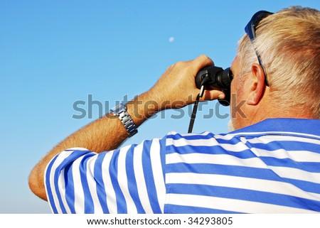 Caucasian man looking through binoculars outdoors - stock photo