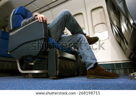 caucasian man passenger in airplane  in comfortable flight and trip of airline - stock photo