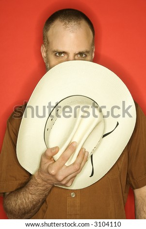 Caucasian man peering over cowboy hat partially covering his face against orange background. - stock photo