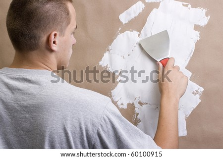 Caucasian man plastering a brown wall with a pallet. - stock photo