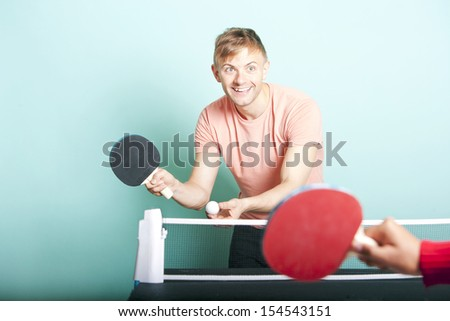 Caucasian man playing table tennis with friend - stock photo