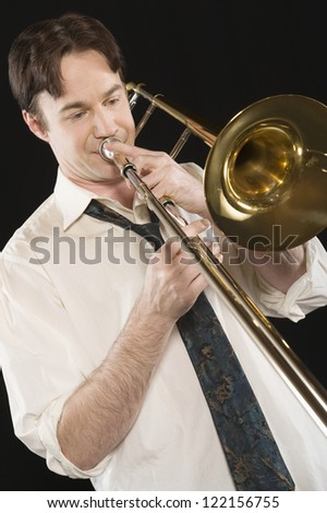 Caucasian  man playing trombone isolated over black background - stock photo