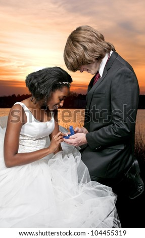 Caucasian man proposing marriage to a black African American woman