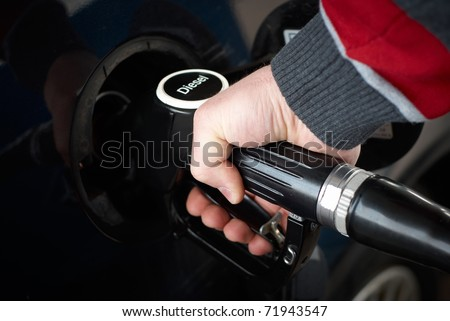 caucasian man refueling a car with diesel