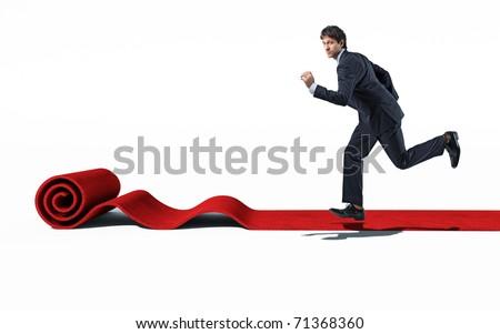 caucasian man running on rolling red carpet - stock photo