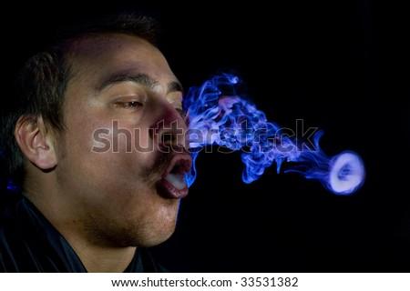 caucasian man smoking in dark room with blue light. - stock photo