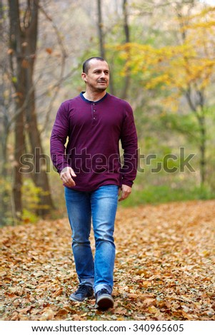 Caucasian man taking a walk in the forest, autumnal landscape - stock photo