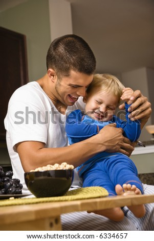 Caucasian man tickling toddler son in kitchen. - stock photo