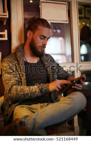 Caucasian man using a digital tablet in cafe.